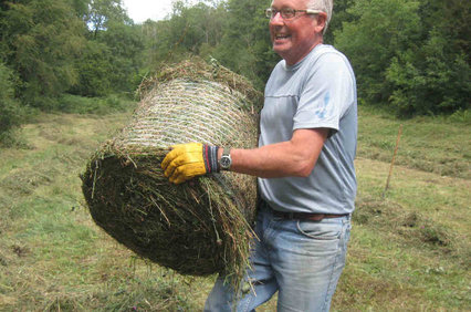 a volunteer is seen carrying a small bale of mown grasses and flowers
